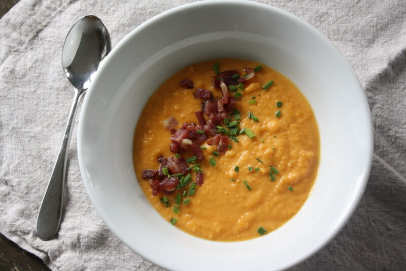 Sweet potato and bacon soup on grey placemat