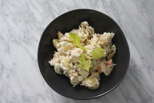 tuna pasta salad in black bowl on marble counter