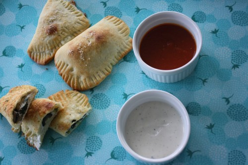 homemade pizza pockets on plate with dipping sauces