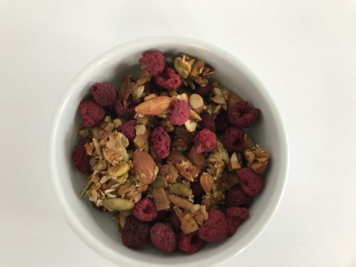 raspberry nut and seed granola in a white bowl