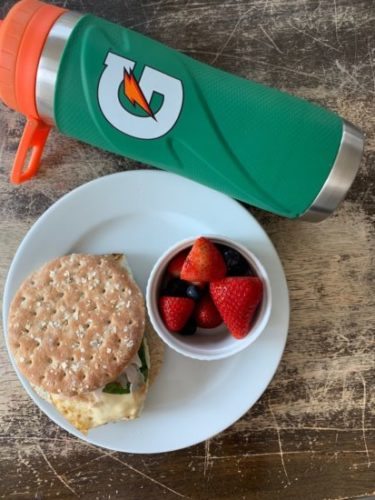 sheet pan egg sandwich with berries and a gatorade water bottle