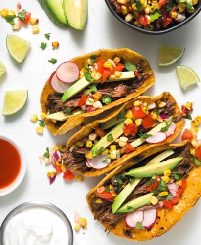 three flank steak tacos with charred corn salsa and avocado