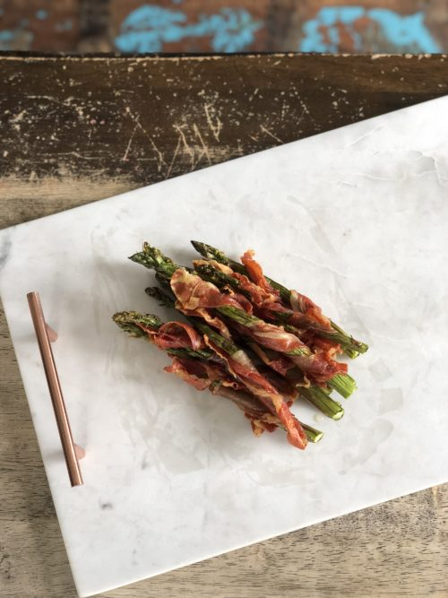 prosciutto wrapped asparagus on marble tray