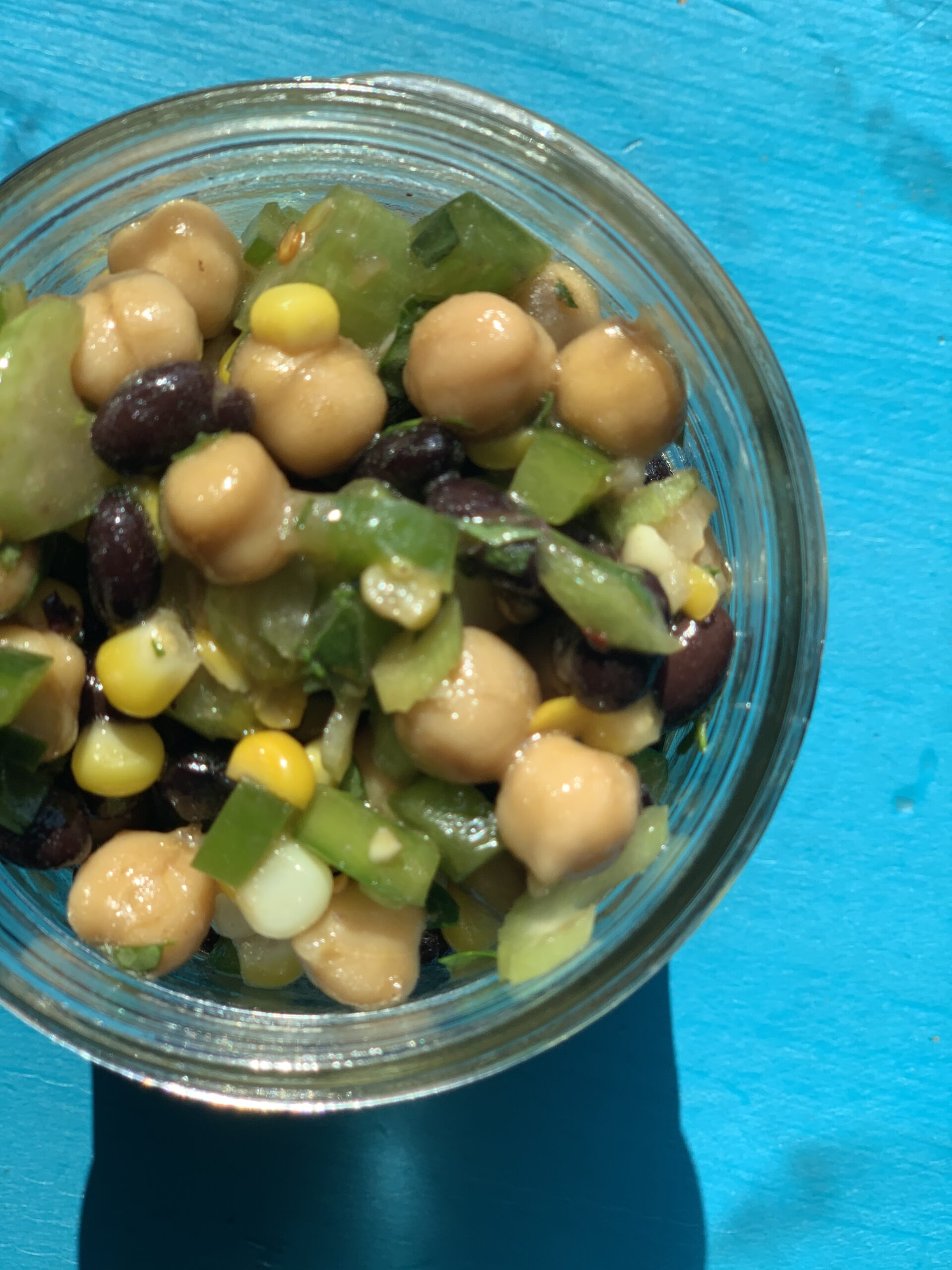 bean salad in bowl with blue background